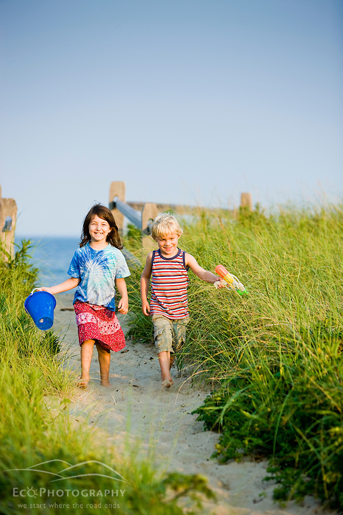 A young brother and sister walk at Center Hill Preserve beach in Plymouth, Massachusetts.