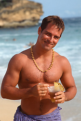 Shirtless man at the beach holding a topical cocktail