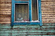 Yakutian pupils are watching out of their class room in the school building in Oymyakon. The area is extremely cold during the winter. Two towns by the highway, Tomtor and Oymyakon, both claim the coldest inhabited place on earth (often referred to as -71.2°C, but might be -67.7°C) outside of Antarctica. The average temperature in Oymyakon in January is -42°C (daily maximum) and -50°C (daily minimum). The images had been made during an outside temperature in between -50°C up to -55°C. Oymyakon, Oimjakon, Yakutia, Jakutien, Russian Federation, Russia, RUS, 20.01.2010