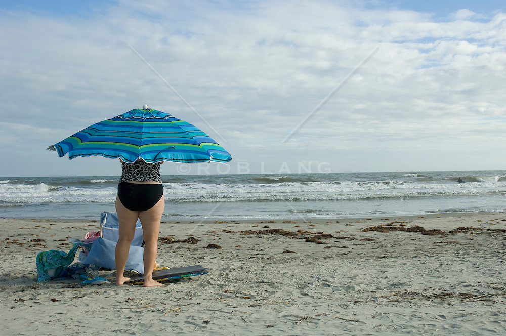Rear view of a woman setting up her beach umbrella in Charleston, SC