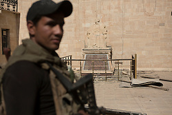 Licensed to London News Pictures. 23/10/2016. An Iraqi Army Counter Terrorism trooper stands guard near a statue defaced by Islamic State militants at the Mart Shmony Church, in Bartella, Iraq.<br /> <br /> Bartella, a mainly Christian town with a population of around 30,000 people before being taken by the Islamic State in August 2014, was captured two days ago by the Iraqi Army's Counter Terrorism force as part of the ongoing offensive to retake Mosul. Although ISIS militants were pushed back a large amount of improvised explosive devices are still being found in the town's buildings. Photo credit: Matt Cetti-Roberts/LNP