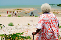 An aboriginal elder woman calls to young children playing in the water on the outskirts of Weipa, far north Queensland, Australia.