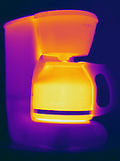 A Thermogram of a coffee machine as it warms up.  This is one image from a series. The different colors represent different temperatures on the object. The lightest colors are the hottest temperatures, while the darker colors represent a cooler temperature.  Thermography uses special cameras that can detect light in the far-infrared range of the electromagnetic spectrum (900?14,000 nanometers or 0.9?14 µm) and creates an  image of the objects temperature..