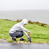 A photograph of a skateboarder setting up a downhill skateboard in Yorkshire, England.