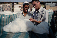 A Han businessman buying cotton from a Uyghur at a market in Kashgar. In the bazaars of Xinjiang Southern crescent Han people are a rare sight.