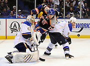 St. Louis Blues' Barret Jackman (5) keeps his eyes on a loose puck as New York Islanders' Matt Martin (17) charges Blues' goalie Jaroslav Halak during an NHL hockey game on Saturday, Jan. 25, 2014, in Uniondale, N.Y. (AP Photo/Kathy Kmonicek)