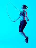 one mixed races woman exercsing jumping rope fitness exercices isolated on blue blackground