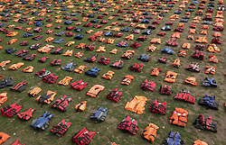 © Licensed to London News Pictures. 19/09/2016. London, UK. A graveyard of life jackets fills Parliament Square ahead of the UN Migration Summit in New York. 2500 of the hi-visibility life jackets abandoned by refugees after crossing from Turkey to the Greek island of Chios have been placed in a grid in the square .  Photo credit: Peter Macdiarmid/LNP