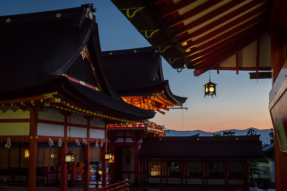 Dusk at the Fushimi Inari shrine is the time for lighting up the lanterns in the main halls.