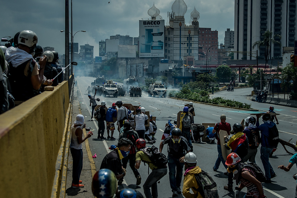 CARACAS, VENEZUELA - MAY 10, 2017:  National guard soldiers fire  tear gas, rubber bullets and buckshot at anti-government protesters who had taken over the Francisco Fajardo highway - the main highway that runs through Caracas. The streets of Caracas and other cities across Venezuela have been filled with tens of thousands of demonstrators for nearly 100 days of massive protests, held since April 1st. Protesters are enraged at the government for becoming an increasingly repressive, authoritarian regime that has delayed elections, used armed government loyalist to threaten dissidents, called for the Constitution to be re-written to favor them, jailed and tortured protesters and members of the political opposition, and whose corruption and failed economic policy has caused the current economic crisis that has led to widespread food and medicine shortages across the country.  Independent local media report nearly 100 people have been killed during protests and protest-related riots and looting.  The government currently only officially reports 75 deaths.  Over 2,000 people have been injured, and over 3,000 protesters have been detained by authorities.  PHOTO: Meridith Kohut