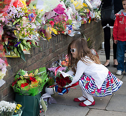 © London News Pictures. A young girl laying flowers at the scene where Drummer Lee Rigby was murdered by two men in Woolwich town centre in what is being described as a terrorist attack. Photo credit: Ben Cawthra/LNP