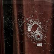 """Photo d'un impact de balle dans une vitre du restaurant """"Le Carillon"""", réalisée le 14 novembre 2015 à Paris au lendemain des attentats parisiens revendiqués par Daesh qui ont fait des dizaines de victimes."""