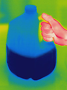Thermogram of milk jug and hand.  The different colors represent different temperatures on the object. The lightest colors are the hottest temperatures, while the darker colors represent a cooler temperature.  Thermography uses special cameras that can detect light in the far-infrared range of the electromagnetic spectrum (900?14,000 nanometers or 0.9?14 µm) and creates an  image of the objects temperature..