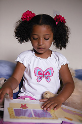 Young girl sitting quietly and reading,