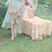Cropped shot of a pale young woman wearing a fancy blue nightgown in the woods and holding a teddybear beside a child's bed
