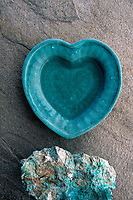 Heart shaped ceramic bowl filled with water set on stone with a turquoise stone.