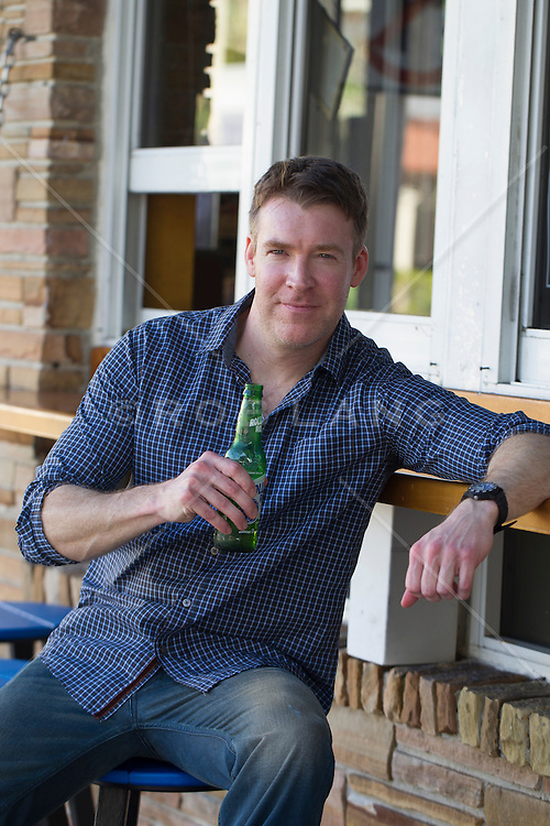 handsome middle aged man enjoying a beer at an outdoor bar in Florida