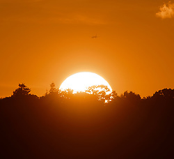 © Licensed to London News Pictures. 15/08/2019.<br /> Orpington ,UK. A plane flying towards the sunset. The sun setting over South East London this evening as more rain has been forecast for tomorrow. Photo credit: Grant Falvey/LNP