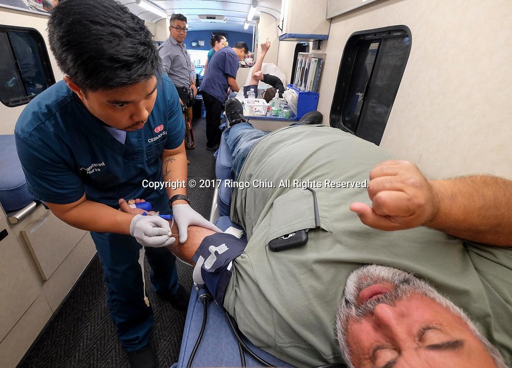 6月14日,在美国洛杉矶,雪松西奈医院的男护士为一名自愿献血者抽血。当日,是世界献血日,为鼓励更多的人无偿献血, 雪松西奈医院特地安排了一辆流献血车停泊在洛杉矶农民市场广场内。新华社发 (赵汉荣摄)<br /> A nurse of Cedars-Sinai Hospital draws blood from a donor during the World Blood Donor Day at a Mobile Blood Drive in Los Angeles, the United States, June 14, 2017. (Xinhua/Zhao Hanrong)(Photo by Ringo Chiu)<br /> <br /> Usage Notes: This content is intended for editorial use only. For other uses, additional clearances may be required.
