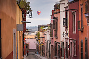 A hot air balloon floats past Spanish colonial style homes in the historic center of San Miguel de Allende, Mexico.