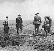 World War I: Army chaplain conducting burial service in the field while burial party stand, paying their respects. c.1916