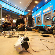 October 31, 2012 - New York, NY : People clutch laptops and cell phones as they sit in the lobby of a Chase Bank at East 41st Street and Third Avenue on Wednesday evening. The location was popular with residents of lower Manhattan who made their way north in search of electricity and internet connections. CREDIT: Karsten Moran for The New York Times