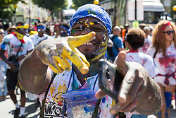 London, August 27 2017. Paint-splattered revellers on Ladbroke Grove as Family Day of the Notting Hill Carnival gets underway. The Notting Hill Carnival is Europe's biggest street party held over two days of the bank holiday weekend, attracting over a million people. © Paul Davey.