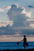 A female silhouetted on the shore walks to her fishing spot with fishing pole, net, and pail in hand.