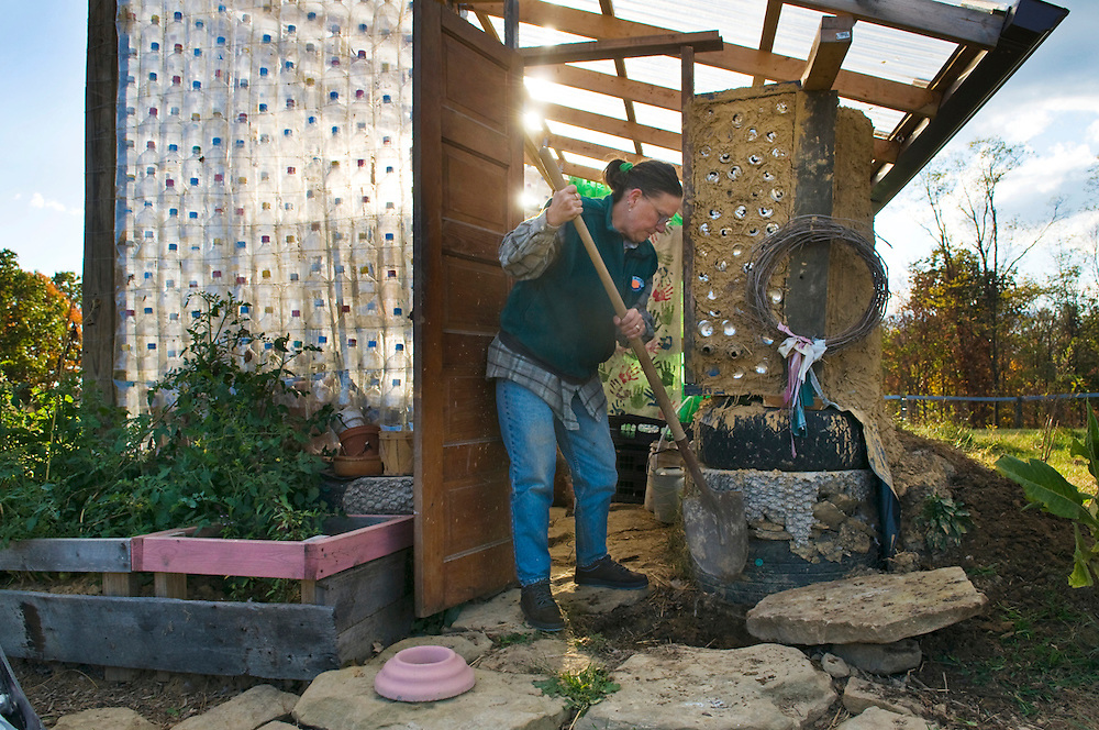 Annie Warmke works on repairing the entryway to the greenhouse. The greenhouse was constructed using over 1,000 plastic bottles and houses plants year-round.