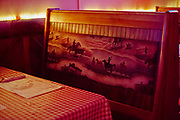 Western scene illustration on the back of a booth in a bar in Columbia Falls, Montana.