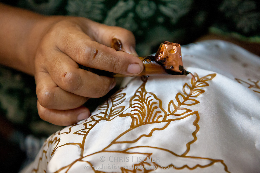 Making batik - detail shot of a woman applying wax using a wax pen called canting. Plentong, Yogyakarta, Central Java, Indonesia.