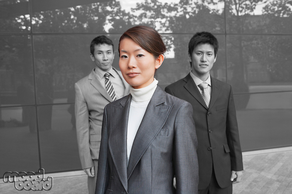 Portrait of young businesswoman with coworkers outside office building