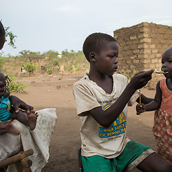 Viola, 16, feeds her 6-month-old daughter Mary, left, next to Bosco,10, who feeds Jennifer, 1, at the Bidi Bidi refugee settlement in Uganda. <br /> 68 percent of the camp's population are children. Many of them have lost or been separated from their parents and are fending for themselves.