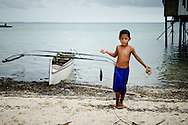 Philippines, Tawi Tawi. Boy from Simunul Island coming back home with a fish.