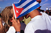 HAVANA, CUBA: Cuban teenagers kiss behind a Cuban flag while they wait for an anti-American protest to start in front of the American Interests Section, the US unofficial embassy in Havana, Cuba, February 22, 2000. Thousands of Cubans marched in front of the interest section to protest the US unwillingness to return Elian Gonzalez to his father in Cuba.    Photo by Jack Kurtz  CROWDS     HUMAN RIGHTS    YOUTH    EDUCATION      CHILDREN     PATRIOTISM