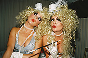 Two identically dressed women wearing blonde wigs, pearls, false-eyelashes and smoking with a cigarette holder, Posh at Addington Palace, UK, August, 2004