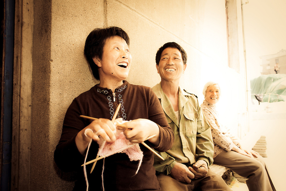 chinese woman knitting and laughing with friends