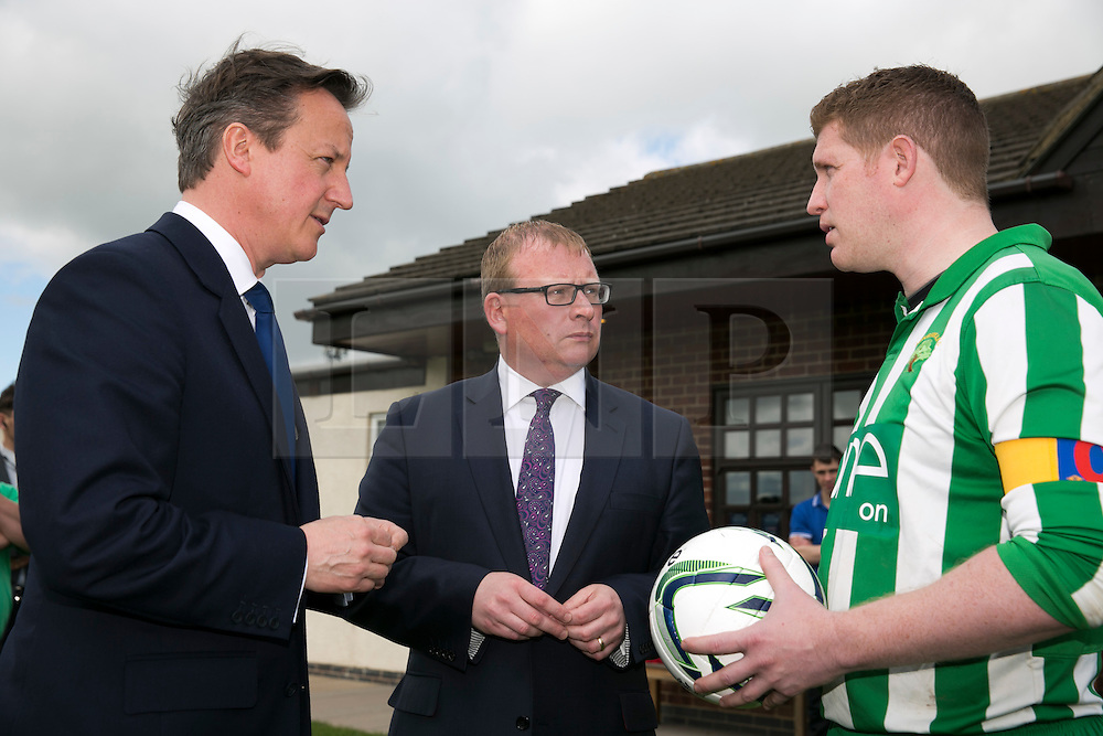 © Licensed to London News Pictures. 03/05/2015. Nuneaton, Warwickshire, UK. The Prime Minister David Cameron visited Ambleside sports club in Nuneaton, Warwickshire, earlier today. Pictured, David Cameron and local MP Marcus Jones, centre, chat to Ambleside FC captain Matt Hall who is raising money in memory of his daughter Georgie who died of Meningitis at 23 months. Photo credit : Dave Warren/LNP
