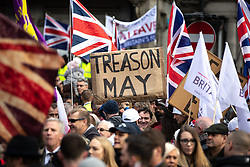 "© Licensed to London News Pictures . 09/12/2018 . London , UK . A banner reading "" Treason May "" in reference to British Prime Minister Theresa May , at a demonstration in support of Brexit , headed by a coalition led by UKIP leader Gerard Batten and former EDL leader Stephen Yaxley-Lennon ( aka Tommy Robinson ) , in Westminster . Photo credit: Joel Goodman/LNP"