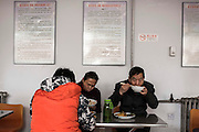 Yiang Zai Yue, diagnosed with alcoholism has lunch with some colleagues inside Vila Rosa Residential Open Unit for people with mental health conditions in Yinqing district, Beijing, China. Photo by Xaume Olleros