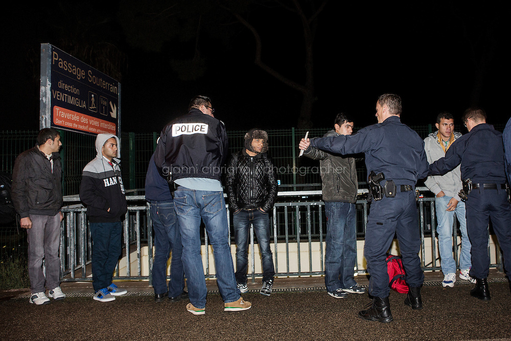 MENTON, FRANCE - 18 NOVEMBER 2014: Migrants are lined up and checked by the French police after being caught in their attempt to cross the Italian-French border by train, in Menton, the first French train stop after Ventimiglia, on November 18th 2014.<br /> <br /> The Ventimiglia-Menton border is the border between Italy and France crossed by migrants who decide to continue their journey up north towards countries such as Germany, Sweden, The Netherlands and the UK where the process to receive the refugee status or humanitarian protection is smoother and faster. in Ventimiglia, Italy, on November 17th 2014.