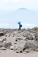 A porter on Mount Kilimanjaro carries his burden in front of a distant Mount Meru in Tanzania.