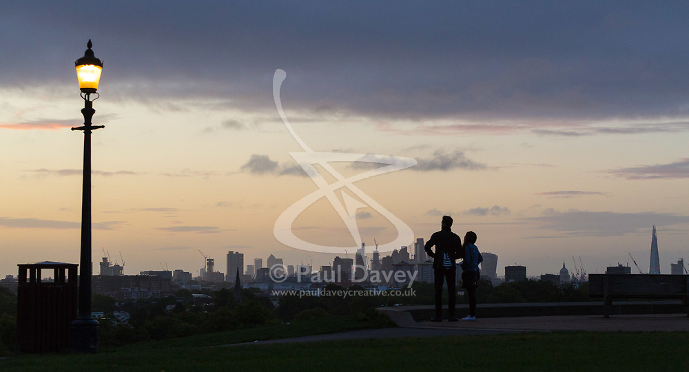London, September 11 2017. A couple wait for the sun to rise above the London skyline as a new day breaks over the city. © Paul Davey