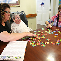 Sissie Craft sits with her parents Maldon and Carolyn Griffin as they put a puzzle together with Maldon at the Green House residents at Traceway Retirement Community.