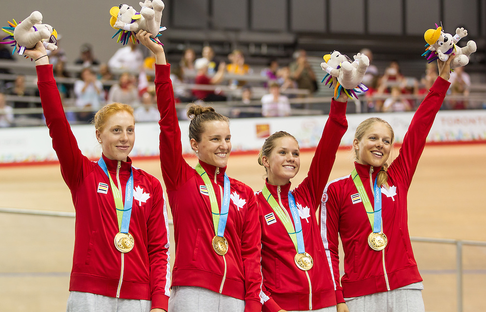 The Canadian gold medal winning team of (L-R) Allison Beveridge, Laura Brown, Jasmin Glaesser and Kirsti Kay wave to the crowd at the velodrome during the medal ceremony for the women's cycling team pursuit at the 2015 Pan American Games in Toronto, Canada, July 17,  2015.  AFP PHOTO/GEOFF ROBINS