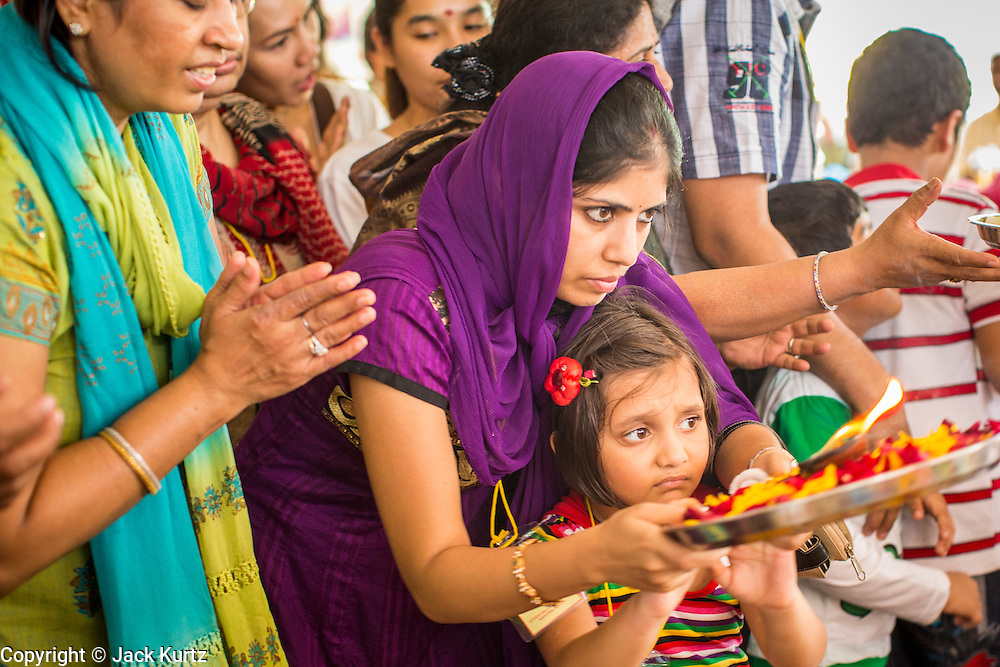 "29 SEPTEMBER 2012 - NAKORN NAYOK, THAILAND:   Thais and Indians seek the blessings of Ganesh during observances of Ganesh Ustav at Wat Utthayan Ganesh, a temple dedicated to Ganesh in Nakorn Nayok, about three hours from Bangkok. Many Thai Buddhists incorporate Hindu elements, including worship of Ganesh into their spiritual life. Ganesha Chaturthi also known as Vinayaka Chaturthi, is the Hindu festival celebrated on the day of the re-birth of Lord Ganesha, the son of Shiva and Parvati. The festival, also known as Ganeshotsav (""festival of Ganesha"") is observed in the Hindu calendar month of Bhaadrapada, starting on the the fourth day of the waxing moon. The festival lasts for 10 days, ending on the fourteenth day of the waxing moon. Outside India, it is celebrated widely in Nepal and by Hindus in the United States, Canada, Mauritius, Singapore, Thailand, Cambodia, Burma , Fiji and Trinidad & Tobago.    PHOTO BY JACK KURTZ"
