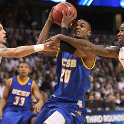 Mar 17, 2011; Tampa, FL, USA; UC Santa Barbara Gauchos forward James Nunnally (21) drives between Florida Gators guard Scottie Wilbekin (5) and guard Kenny Boynton (1) during second half of the second round of the 2011 NCAA men's basketball tournament at the St. Pete Times Forum. Florida defeated UCSB 79-51.  Mandatory Credit: Derick E. Hingle