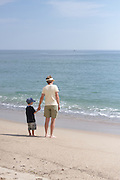 A five-year-old boy and his grandmother watch the surf and gaze at the Atlantic Ocean, Cahoon Hollow Beach on the Cape Cod National Seashore, Wellfleet, Massachusetts.