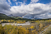 A rainbow brightens clouds over the Highwood Creek Area, in Kananaskis Country, Canadian Rockies, Alberta, Canada. Mountains in the background are in Don Getty Wildland Provincial Park.