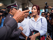 22 MAY 2015 - BANGKOK, THAILAND: A Thai police officer gestures while anti-coup activists SIRIWAT SERITHIWAT (center partially blocked) and NATCHACAH KONG-UDOM (right) talk to a Thai police officer at Lat Phrao subway at the start an anti-coup protest.  The Thai military seized power in a coup on May 22, 2014. There were small protests throughout Bangkok Friday to mark the first anniversary of the coup. Police arrested protestors at several locations. The most serious protest was at Bangkok Art and Culture Centre (BACC) where about 100 protestors, mostly students, faced off against police for several hours. Police made numerous arrests at the BACC protest.     PHOTO BY JACK KURTZ